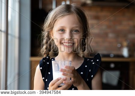 Cheerful Little Girl With Milk Mustache Holding Glass Of Yoghurt