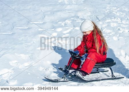 Child Enjoying The Ski Slopes. Little Girl Enjoy A Sleigh Ride. Toddler Kid Girl Riding A Sledge. Ch