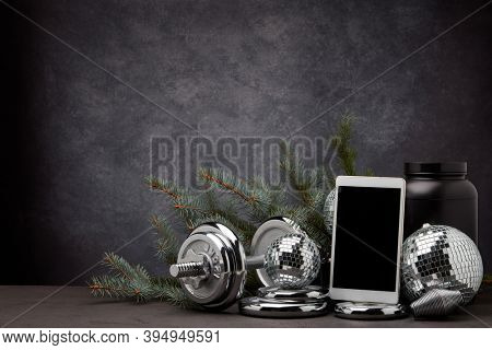 Sports nutrition, sports equipment, fir branch, Christmas ornament, blank computer tablet on dark grey background with copy space. Fitness, sport or healthy lifestyle concept. New Year and Christmas.