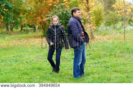 father and daughter walking outdoor in autumn city park, no emotion and unhappy, walk separately, this is the problem of poor communication