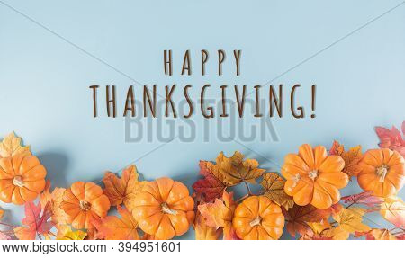 Thanksgiving Background Decoration From Dry Leaves And Pumpkin On  Pastel Blue Background. Flat Lay,