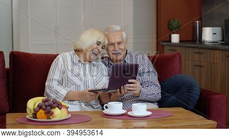 Senior Old Grandparents Couple Talking And Using Digital Laptop Computer At Home. Online Shopping. E