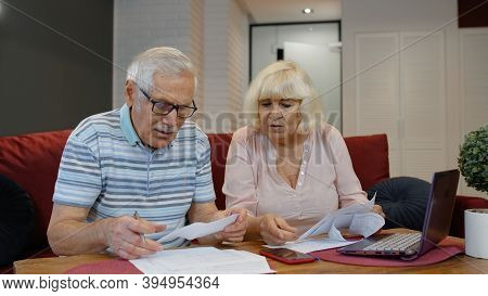 Worried Senior Old Couple Stressed About Paperwork Discuss Unpaid Bank Debt Holding Bills Check Expe