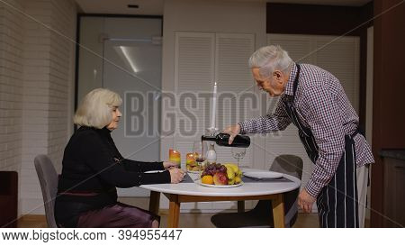 Senior Retired Couple Having Fun Drinking Wine And Eating Healty Meal During Romantic Supper Sitting