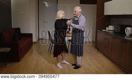 Happy Senior Couple In Love Have Romantic Evening, Dancing Together In The Kitchen At Home, Celebrat