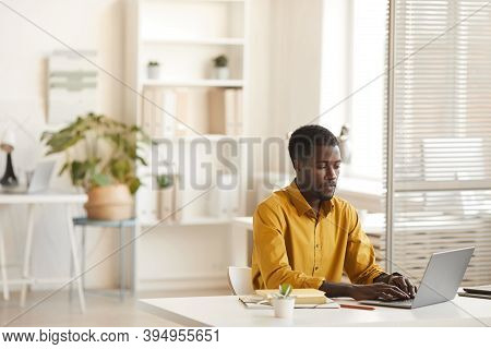 Wide Angle View At Contemporary African-american Man Using Laptop While Working At Desk In Minimal O