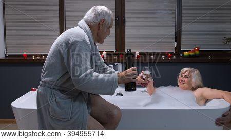 Sexy Senior Woman Grandmother Is Taking Foamy Bath In Luxury Bathroom With Candles. Elderly Grandfat