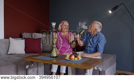 Modern Trendy Elderly Couple Smoking Hookah At Home. Senior Grandmother And Grandfather Having Fun R