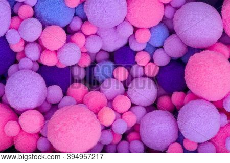 Background From Multi-colored Pom-poms Of Different Sizes. Pink, Violet And Violet Furry Pom-pons In