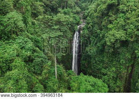 Aerial Drone View Of Large Hidden Waterfall In Jungle Rainforest. Wild Untouched Nature, Green Backg