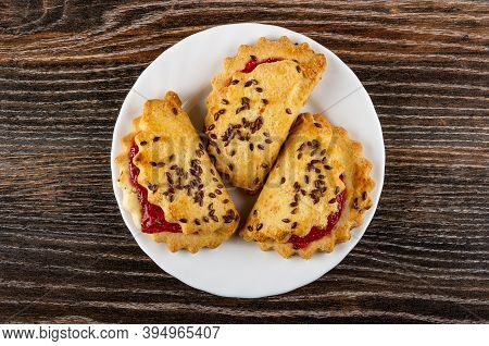 Three Shortbread Cookies With Raspberry Jam And Linseeds In White Plate On Dark Wooden Table. Top Vi