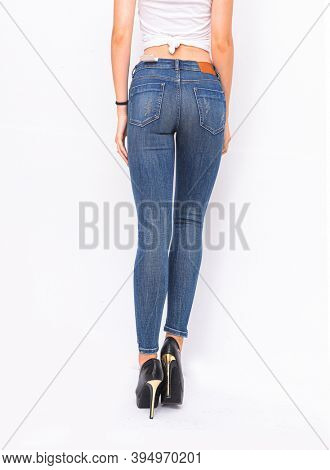 Back view Young woman in white shirt with blue jeans and black high heels shoes posing