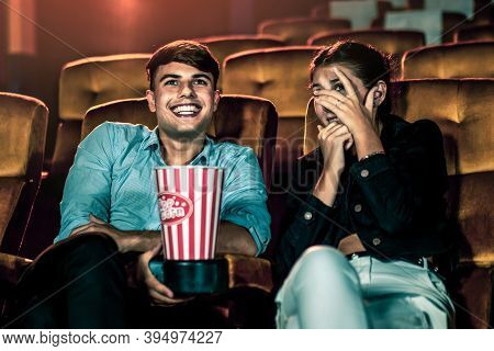 A Couple Of Caucasian Watch A Thriller Movie In The Cinema, Woman Eyes Closed And Turning Her Face A