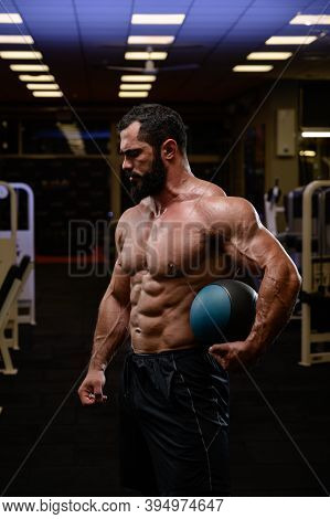 Strong Caucasian Male With Beard Holding Heavy Medicine Ball In Sport Fitness Gym