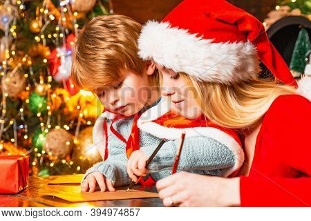 Mum And Kid Writing A Letter To Santa With Wish List Of Christmas Presents.christmas Interior. Merry