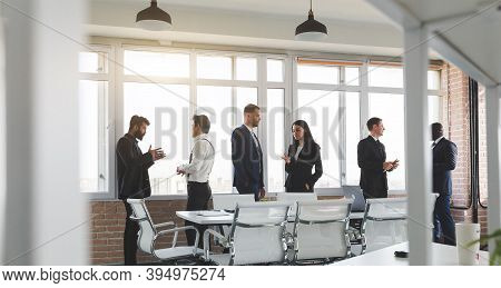 Businesspeople Against The Window. A Team Of Young Businessmen Working And Communicating Together In
