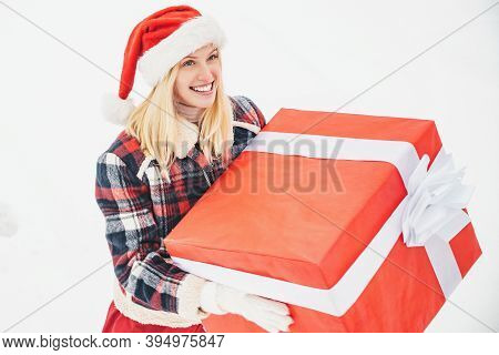 Santa Woman Holds A Big Gift Box With Copy Space For Your Text. Christmas Girl Holding A Big Gift. B