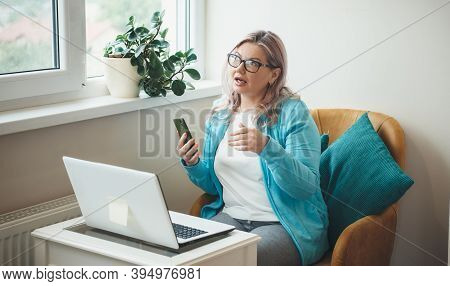 Busy Senior Woman With Blonde Hair And Glasses Is Having Online Meeting O Laptop Working From Home