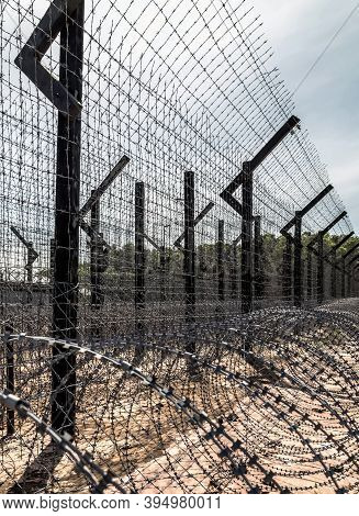 Barbwire Metal Fence Is Electrified Barrier Of The Prison. Fence With Metal Barbed Electricity Wire