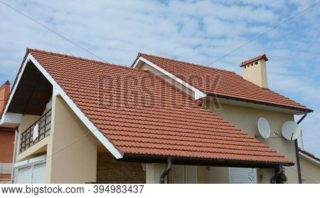 A Close-up On A Stucco House With A Red Metal Tiled Double Gabled Roof, A Chimney, Fascia Boards, Ra