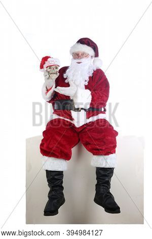 Santa Claus. Santa Claus is holding a Human Skull wearing a 1st Christmas Hat. Isolated on white. Room for text. Even Skeletons enjoy Christmas.