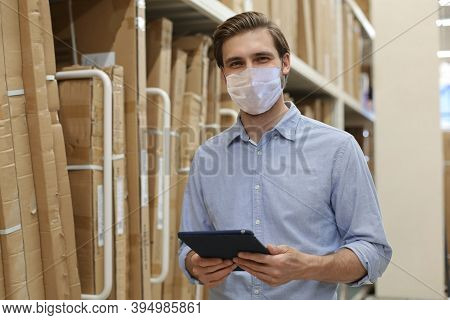 Manager Wears Preventive Mask Use His Tablet For Online Checking Products Available.