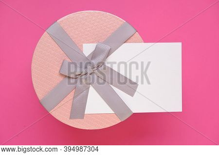 Gift And Postcard For The Holiday. Round Box With Bow And Blank Postcard On Bright Pink Background.c