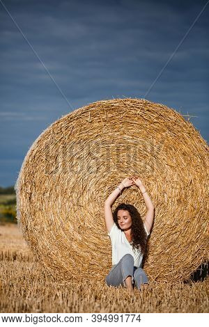 Beautiful Young Woman Near A Sheaf Of Hay In A Field. Holidays In The Village, A Girl Enjoying Natur