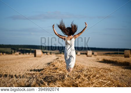 Young Curly-haired Woman In A Wheat Field, Where There Is A Huge Sheaf Of Hay, Enjoying Nature. Peop