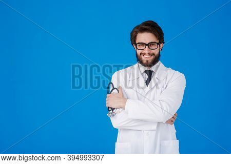A Young Bearded Doctor On A Blue Background In A White Coat Looks At The Camera. Covid-19. Self Isol