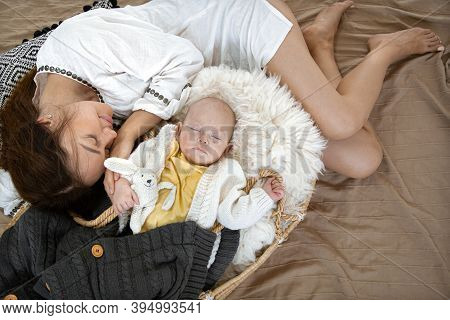Mom And Baby Are Sleeping. Little Boy In A Wicker Cradle With A Toy On The Background Of A Blanket.