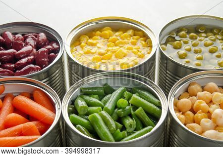 Canned Carrots, Chickpeas, Kidney Beans, Green Beans, Peas And Corn In Opened Tin Cans On Kitchen Ta