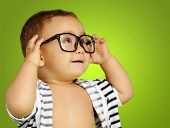 Portrait Of Baby Boy Wearing Eyeglasses against a green background poster