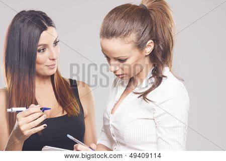 Two beautiful businesswomen discussing