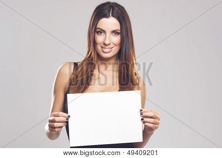 Beautiful brunette woman holding white blank sign