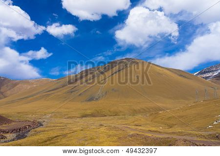 Picturesque hill against the background of colourful dark blue sky with clouds
