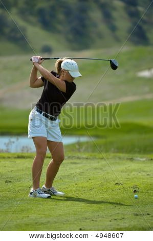 Woman Golfer Swinging A Driver On The Tee Box