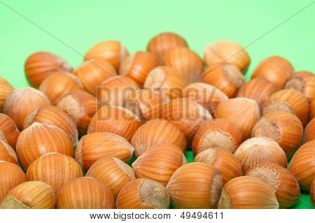 close-up of whole hazelnuts on green background