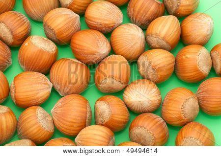 close-up of whole hazelnuts on green background