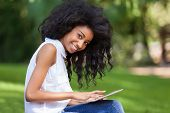 Outdoor portrait of a smiling teenage black girl using a tactile tablet - African people poster