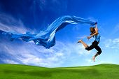 Beautiful athletic woman jumping on a green meadow with a scarf poster