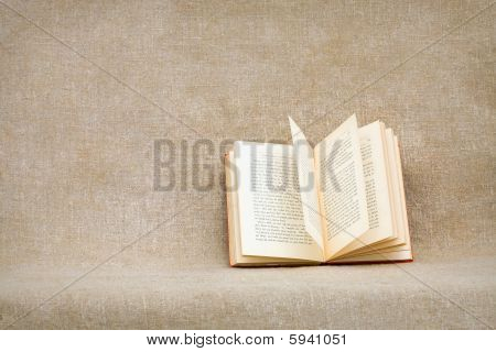 Open Old Book On A Rough Brown Sacking