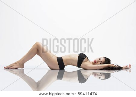 Beautiful Asian Girl laying on reflective surface