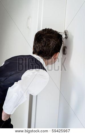 Boy looking through a keyhole