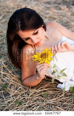Beautiful girl with sunflower in the hay.