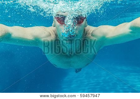 Man in swim cap and googles under water in swimming pool poster