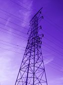 A purple toned duo-tone of a high voltage electrical tower. poster