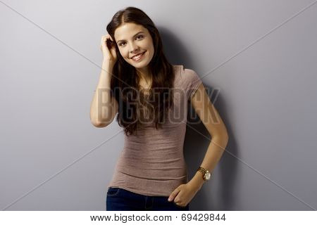 Portrait of happy young woman standing by grey wall, smiling, looking at camera.