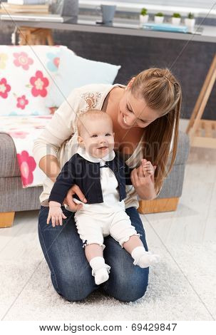 Young mother kneeling on floor at home with little baby girl on lap.