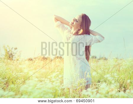 Beauty Girl Outdoors enjoying nature. Beautiful Teenage Model girl in white dress having fun on summer Field with blooming flowers, Sun Light. Sunrise. Glow Sun. Free Happy Woman